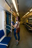 Smiling girl standing in subway train at metro royalty free stock photos