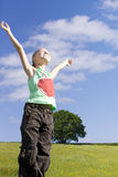Smiling girl standing in sunny field with arms raised Royalty Free Stock Photo