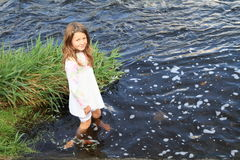 Smiling girl standing in water Stock Photos