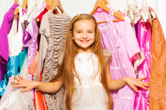 Smiling girl stands among dresses on hangers Stock Images