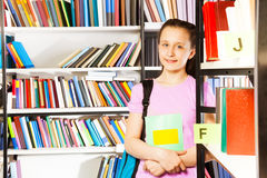 Smiling girl stands near bookshelf with textbook Royalty Free Stock Images