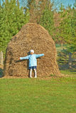Smiling girl stands near haystacks Royalty Free Stock Photo