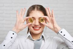 Smiling girl holds two golden bitcoins on the white background. Royalty Free Stock Photos