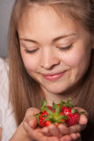 Smiling Girl Staring at Strawberries on her Hands Royalty Free Stock Images