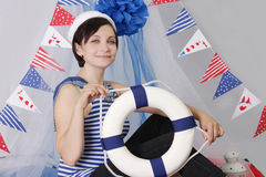 Smiling girl with steering wheel and marine decor Royalty Free Stock Photo
