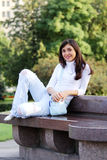 Smiling girl on stone bench Stock Image