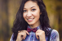 Smiling girl straightens bow tie Royalty Free Stock Photography