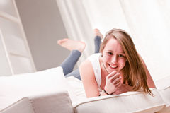 Smiling girl in a strange position on a couch Stock Photos