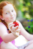 Smiling girl with strawberry. Portrait of smiling girl with focus on partially eaten strawberry in foreground Royalty Free Stock Photos