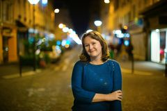 Smiling girl on a street at night Stock Images