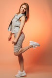 Smiling girl in a striped dress and a denim vest standing with her leg raised. On orange background Royalty Free Stock Photography