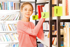 Smiling girl in striped shirts stands near shelf Royalty Free Stock Photos