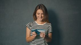 Girl Reads Information on Ticket. Smiling girl in striped t-shirt reading information on ticket, isolated shot in the grey background stock video footage