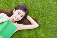 Smiling girl student  laying down  on a meadow Stock Photos