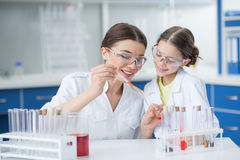 Smiling girl student watching scientist teacher making experiment in lab Stock Images