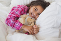 Smiling girl with stuffed toy resting in bed Royalty Free Stock Photography
