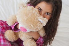 Smiling girl with stuffed toy sitting on bed Stock Image