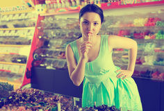 Smiling girl suck candy at sweets store Royalty Free Stock Photos