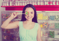 Smiling girl sucking   lollypop in  store. Portrait of  girl  with lollypop at candies shop Stock Photo
