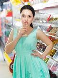 Smiling girl sucking   lollypop in  store. Portrait of  girl  with lollypop at candies shop Royalty Free Stock Photography
