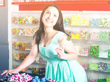 Smiling girl sucking   lollypop in  store. Pretty girl sucking   lollipop in the sweets store Stock Photography