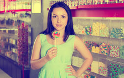 Smiling girl sucking   lollypop in  store. Pretty girl sucking   lollipop in the sweets store Stock Images