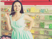 Smiling girl sucking   lollypop in  store. Pretty girl sucking   lollipop in the sweets store Royalty Free Stock Photo