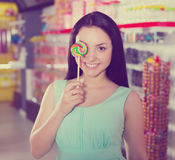 Smiling girl sucking   lollypop in  store. Pretty girl sucking   lollipop in the sweets store Royalty Free Stock Images