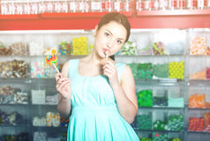 Smiling girl sucking   lollypop in  store. Young woman  sucking lolly  in candies shop Stock Photos