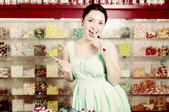 Smiling girl sucking   lollypop in  store. Young woman  sucking lolly  in candies shop Royalty Free Stock Photos