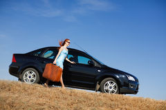 Smiling girl and suitcase. Laughing girl with the suitcase near the car Stock Photos