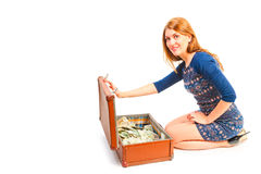 Smiling girl and suitcase full of money Stock Image