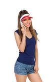 Smiling Girl In Sun Visor Cap On the Phone. Smiling girl in blue shirt, jeans shorts and red sun visor cap using the phone. Three quarter length studio shot Royalty Free Stock Photos
