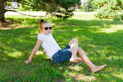 Smiling girl in sunglass with sore knee Stock Image