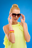 Smiling girl in sunglasses on blue background. Stock Photography