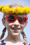 Smiling girl in sunglasses and dandelion garland Stock Image