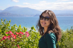 Smiling girl with sunglasses, natural lake mountains landscape with flowers and trees, woman model in nature Stock Image