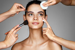 Smiling girl surrounded by hands of makeup artists with brushes,cotton sponge and moisturizer cream near her face. Stock Photography