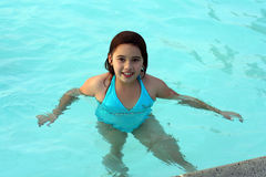Smiling girl in swimming pool. A smiling 6-year-old girl stands in a swimming pool. She has big brown eyes and brown hair and is of Asian and Caucasian Stock Image