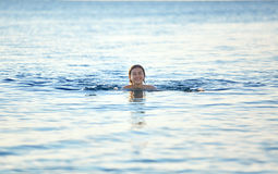 Smiling girl swims in the sea at dawn Royalty Free Stock Image