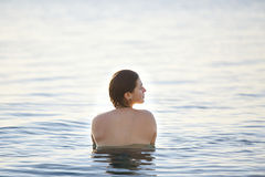 Smiling girl swims in the sea at dawn Stock Photo