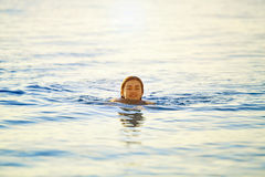 Smiling girl swims in the sea at dawn Royalty Free Stock Photos