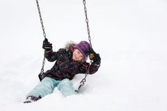 Smiling Girl on Swing in Deep Snow Royalty Free Stock Photography