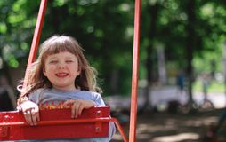 Smiling girl on the swing royalty free stock image