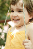 Smiling girl in swings closeup Stock Photos