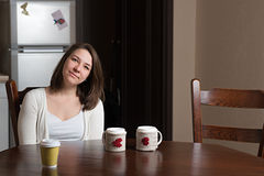 A smiling girl is at a table. Smiling girl sits at table and drinking coffee Stock Photo