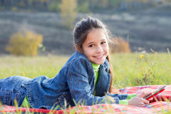 Smiling girl with tablet PC. On the autumn landscape, outdoors Stock Image