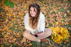 Smiling girl with tablet pc on the autumn landscape, outdoors Royalty Free Stock Images