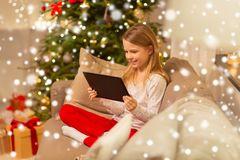 Smiling girl with tablet pc at christmas home royalty free stock photo