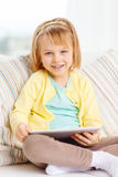 Smiling girl with tablet pc computer at home Royalty Free Stock Images